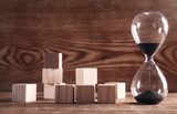 Hourglass with wooden cubes on wooden background.