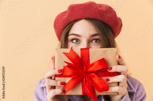 Leinwandbild Motiv Image of brunette woman 20s with long hair smiling and holding gift box, standing isolated over beige background
