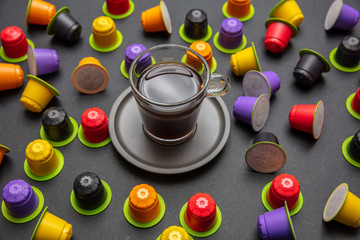Coffee cup and compostable capsules, on black color background