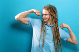 Powerful young man in a success flex pose on a solid background - 244739937
