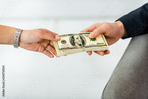 cropped view of businesswoman giving dollar banknotes to businessman in office
