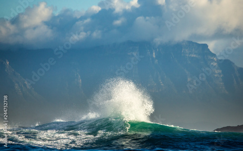 Big waves break on the rocks in the sea against the backdrop of the coastline. Beautiful seascape.  A beautiful moment. Very dynamic photo. Cape Town. False Bay. South Africa.