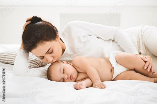 Mother kissing her sleeping newborn baby in bed © Prostock-studio