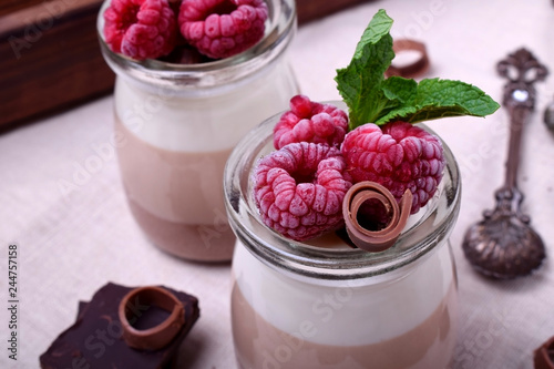 Three chocolate mousse dessert in a glass jar garnished with frozen raspberries and mint