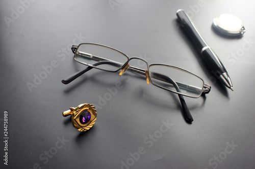 Still life, business, office supplies or education concept: a view of a recumbent padding, glasses, a pen, a clock, accessories against a dark background, ready to add or layout © игорь перекрестоd