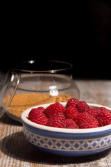Bowl of raspberries on wooden background