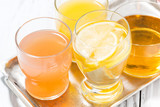 assortment of fresh citrus juices in glasses on white table, top view closeup - 244771517