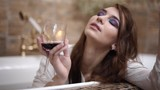 Dreamy young woman in white shirt drinks red wine from high glass sitting in luxary bath and smiles close up. - 244787762