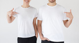 Smiling young couple pointing at blank white t-shirts with index fingers, copy space for your advertising, isolated on gray background - 244803309