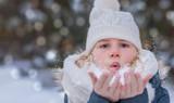 Kind pustet Schnee wie Wunschstaub von den Händen, im Hintergrund verschwommener Winterbokeh - 244816152