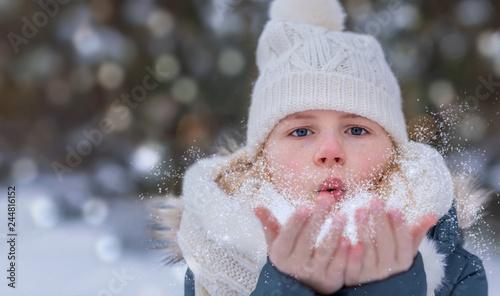 Leinwandbild Motiv Kind pustet Schnee wie Wunschstaub von den Händen, im Hintergrund verschwommener Winterbokeh