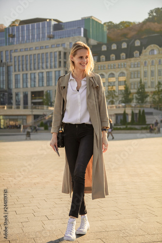 fototapeta na ścianę A young successful woman in a trench coat, walking in the street, holding phone.