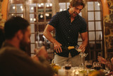 Man serving champagne to friends during party - 244827798
