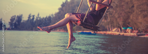 slender female legs close up, woman swinging on a swing on the beach during sunset, rest, travel, lifestyle concept - 244857949