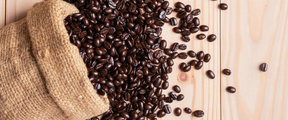 .Coffee beans spilled out from linen sack © anankkml