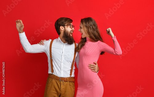 Leinwanddruck Bild couple of emotional people man and woman on red background.