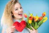 Fototapeta Tulipany - Woman holds tulips and red heart © Voyagerix