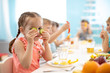 funny children eating healthy food in kindergarten or daycare