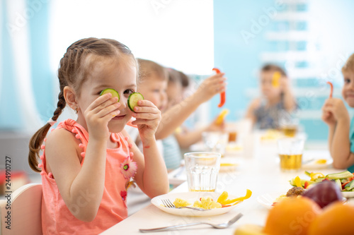 funny children eating healthy food in kindergarten or daycare - 244910727