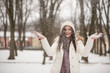 Young beautiful woman is enjoying the snow scattering it in the air. Winter outdoor activities, positive emotions, joy and happiness