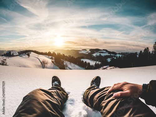 Pov view of young man looking the sunset on snow high mountains - 244937929