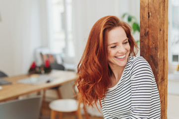 Laughing carefree young woman indoors at home