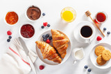 Continental breakfast with croissant, jam, chocolate spread and coffee. Top view