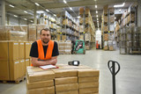 smiling workers in a warehouse of a forwarding agency - trade and delivery of goods // Portrait lächelnder Arbeiter in einem Warenlager einer Spedition - Handel und Lieferung von Gütern //
