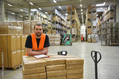Leinwandbild Motiv smiling workers in a warehouse of a forwarding agency - trade and delivery of goods // Portrait lächelnder Arbeiter in einem Warenlager einer Spedition - Handel und Lieferung von Gütern //