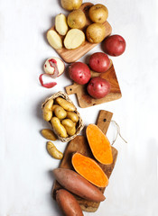 Variety of raw uncooked organic potatoes: red, white, sweet  and fingers potatoes over dark texture background.