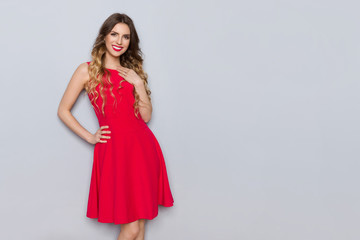 Beautiful Woman In Red Dress Is Holding Hand On Chest And Smiling
