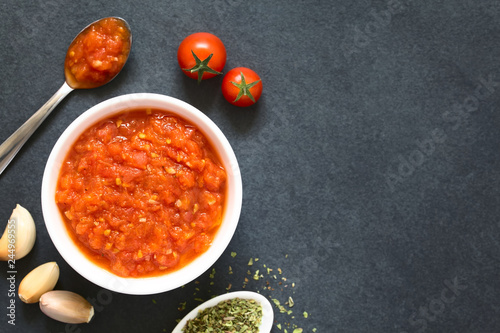 Foto Murales Homemade traditional Italian marinara or pomodoro tomato sauce made of fresh tomato, garlic, dried oregano and salt, photographed overhead on slate with natural light (Selective Focus on the sauce)