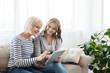 Leinwandbild Motiv Senior mother and daughter browsing internet on tablet