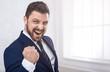 Leinwandbild Motiv Businessman celebrating victory shouting happily in office
