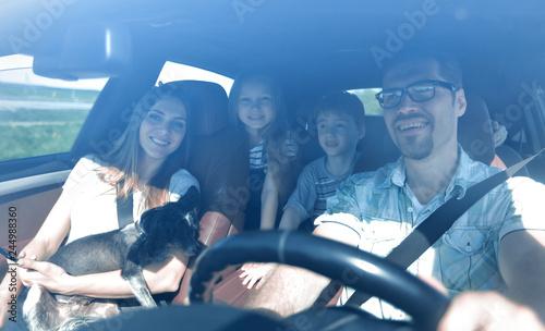 Leinwandbild Motiv family with two children traveling in a family car