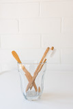 Fototapeta Sypialnia - Close up of bamboo toothbrushes in glass on white table against brick wall (selective focus) © Natalie Board