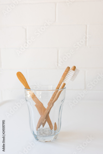 Close up of bamboo toothbrushes in glass on white table against brick wall (selective focus)