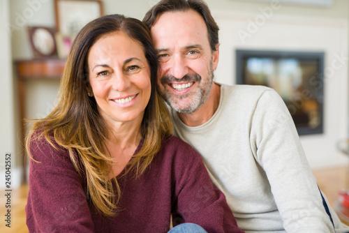 Leinwandbild Motiv Beautiful romantic couple sitting together on the floor at home