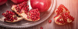 Cuted fresh pomegranate fruits on wooden rustic background. banner maket. selective focus