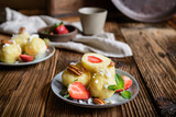 Sweet dumplings stuffed with strawberries topped with curd