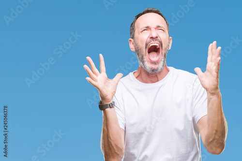 Leinwandbild Motiv Middle age hoary senior man wearing white t-shirt over isolated background crazy and mad shouting and yelling with aggressive expression and arms raised. Frustration concept.