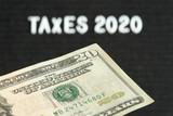 Ein Dollar Geldschein und die Steuern im Jahr 2020 in Amerika