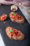 Bruschetta sandwiches with tomato, basil leaf and garlic on gray board as background