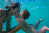 Fototapeta Łazienka - Happy mother playing with infant boy in beautiful tropical sea water with white sand, activity in vacation, underwater shot at Maldives, baby diving underwater © willyam