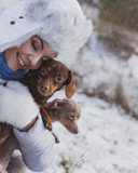 Fototapeta Psy - Woman playing with dogs during winter © anetlanda