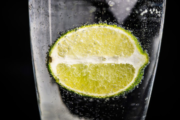 lime in a glass with water with bulbs, background