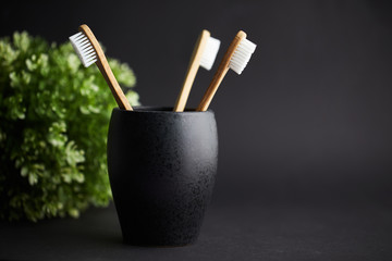 Three bamboo toothbrushes in a black glass with copy space on a dark background © Rostislav Sedlacek