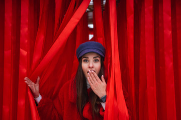 Woman looks out between red curtain.