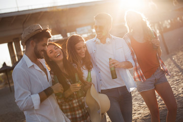 Group of young cheerful friends walking and drinking beer