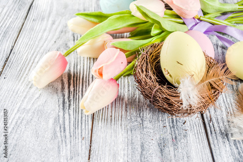 Pastel Easter background with tulip flowers and colorful painted Easter eggs. Top view, rustic white wooden table. Background for greeting card. Copy space for text